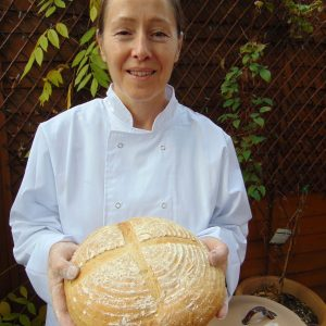 Brenda Daly, founder of Daly Bread, holding a home baked loaf